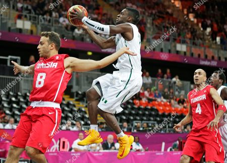 Tony Skinn, Marouan Kechrid Nigeria's Tony Skinn, center, drives to the basket behind Tunisia's Marouan Kechrid, left, during a basketball game at the 2012 Summer Olympics, in London. At right is Tunisia's Radhouane Slimane