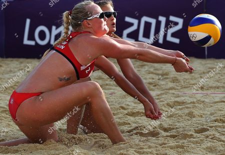 Zara Dampney, right, from Great Britain celebrates with her teammate Shauna Mullin, left, reach for a ball during the Beach Volleyball match against Canada at the 2012 Summer Olympics, in London