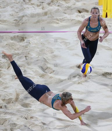 Stock Photo of Tamsin Hinchley, right, from Australia looks on as her teammate Natalie Cook, left, dives for a ball during their Beach Volleyball match against Austria at the 2012 Summer Olympics, in London