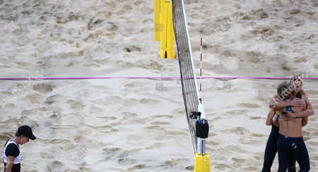 Doris Schwaiger, left, from Austria walks past Natalie Cook, center, and Tamsin Hinchley, right, from Australia as they react during their Beach Volleyball match at the 2012 Summer Olympics, in London