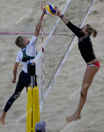 Kerri Walsh of the United States blocks the shot of Australia's Natalie Cook during a beach volleyball match at the 2012 Summer Olympics, in London