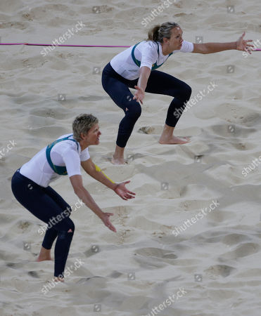 Australia's Natalie Cook, left, and teammate Tamsin Hinchley take defensive positions near the end of a loss to the United States during a beach volleyball match at the 2012 Summer Olympics, in London