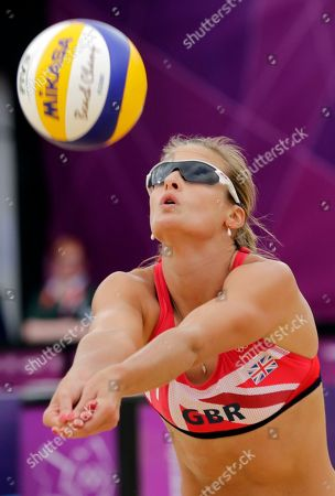 Zara Dampney of Great Britain sets the ball during a beach volleyball match against Italy at the 2012 Summer Olympics, in London
