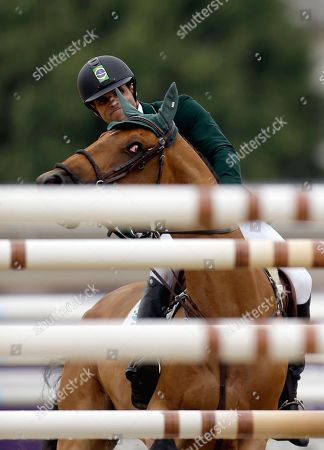 Stock Photo of Carlos Motta Ribas Wilexo, ridden by Carlos Motta Ribas, of Brazil, turns away from jumping a pole during the equestrian individual show jumping competition at the 2012 Summer Olympics, in London