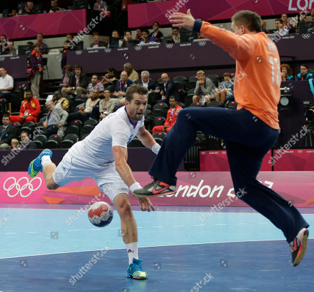 Goalkeeper Robert White of Graet Britain tries to stop a shot by Guillaume Gille of France during their men's handball preliminary match at the 2012 Summer Olympics, in London