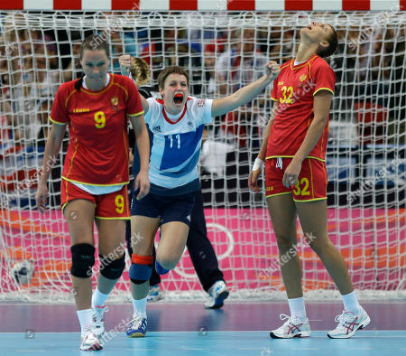 Lyn Byl of Great Britain celebrates after scoring next to Montenegro's Ana Radovic, left, and Katarina Bulatovic during their women's handball preliminary match at the 2012 Summer Olympics, in London