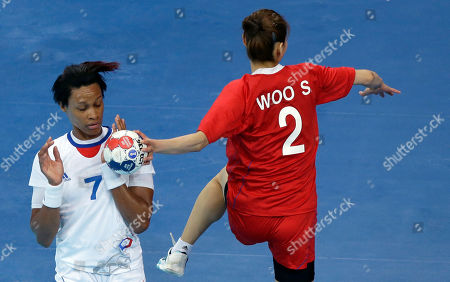 Allison Pineau of France closes her eyes as Woo Sun-hee try to shoot during their women's handball preliminary match at the 2012 Summer Olympics, in London