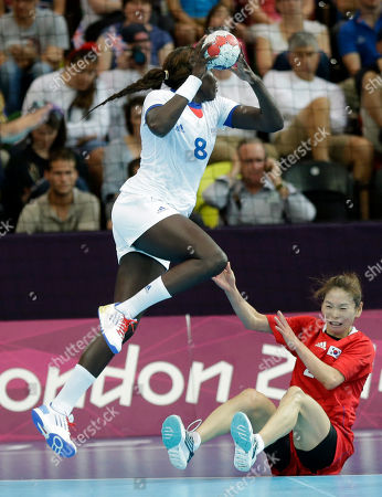Claudine Mendy of France jumps over Woo Sun-hee of South Korea during their women's handball preliminary match at the 2012 Summer Olympics, in London