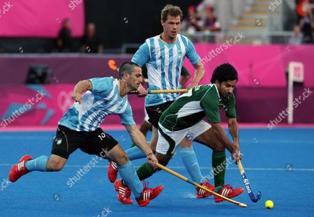 Lucas Vila, Fareed Rizwan Argentina's Santiago Montelli, front, and Pakistan's Ahmed Waseem vie for the ball during their men's hockey preliminary match at the 2012 Summer Olympics, in London