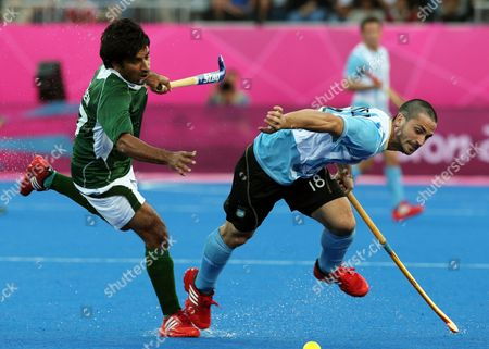 Lucas Vila, Fareed Rizwan Argentina's Santiago Montelli, front, and Pakistan's Ahmed Waseem vie for the ball in the men's hockey preliminary match at the 2012 Summer Olympics, in London