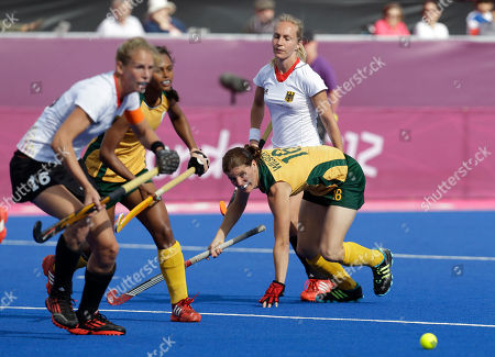 South Africa's Jennifer Wilson, right, passes the ball during a women's hockey preliminary round match against Germany at the 2012 Summer Olympics, in London. Germany won the match 2-0