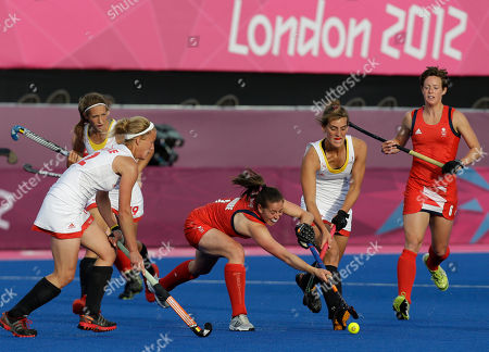 Britain's Emily Maguire, center, fights for the ball during a women's hockey preliminary round match against Belgium, at the 2012 Summer Olympics, in London. Great Britain won the match 3-0