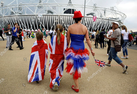 Anna Prior, right, walks with her children Detty Prior, center, and Johnny Prior toward Olympic Stadium to watch the Opening Ceremony at the 2012 Summer Olympics, in London