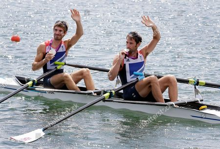 Great Britain's Mark Hunter and Zac Purchase wave to the grandstand after winning the silver medal for the lightweight men's rowing double sculls in Eton Dorney, near Windsor, England, at the 2012 Summer Olympics