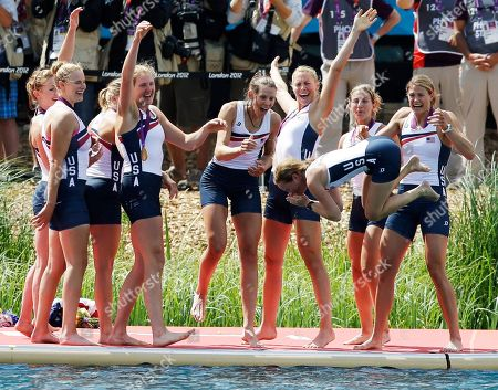 U.S. rowers from left to right, Caryn Davies, Caroline Lind, Eleanor Logan, Meghan Musnicki, Taylor Ritzel, Esther Lofgren, Zsuzsanna Francia, and Erin Cafaro throw coxswain Mary Whipple into the water after winning the gold medal for the women's rowing eight in Eton Dorney, near Windsor, England, at the 2012 Summer Olympics