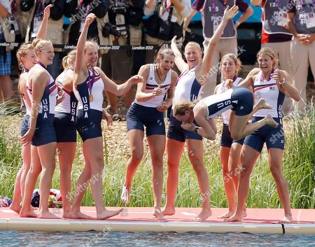 Stock Picture of U.S. rowers Caryn Davies, Caroline Lind, Eleanor Logan, Meghan Musnicki, Taylor Ritzel, Esther Lofgren, Zsuzsanna Francia, and Erin Cafaro throw coxswain Mary Whipple into the water after winning the gold medal for the women's rowing eight in Eton Dorney, near Windsor, England, at the 2012 Summer Olympics