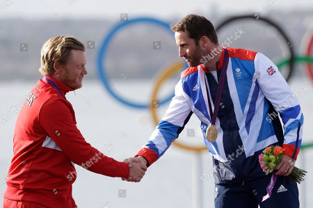 Gold medalist Ben Ainslie of Great Britain, right, shakes hands with Denmark's Jonas Hogh-Christensen during the finn class medal ceremony at the London 2012 Summer Olympics, in Weymouth and Portland, England