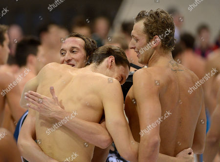 France's Fabien Gilot, left at back, France's Amaury Leveaux, right, and France's Clement Lefert react after winning gold in the men's 4x100-meter freestyle relay final at the Aquatics Centre in the Olympic Park during the 2012 Summer Olympics in London