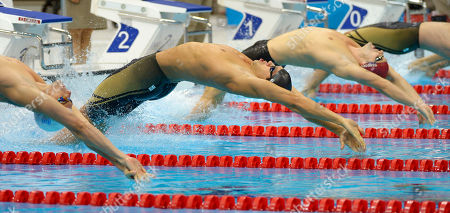 France's Camille Lacourt, left, United States' Matthew Grevers, center, and Britain's Liam Tancock start in the men's 100-meter backstroke swimming final at the Aquatics Centre in the Olympic Park during the 2012 Summer Olympics in London