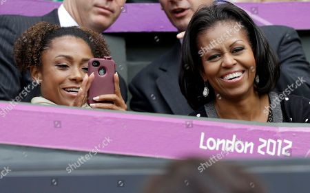 First lady Michelle Obama, right, smiles as former USA gymnast Dominique Dawes snaps a photo as they watch Serena Williams of the United States compete against Jelena Jankovic of Serbia at the All England Lawn Tennis Club in Wimbledon, London at the 2012 Summer Olympics