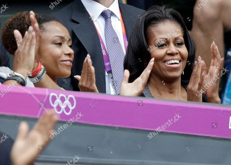 First lady Michelle Obama, right, applauds with former USA gymnast Dominique Dawes as they watch Serena Williams of the United States compete against Jelena Jankovic of Serbia at the All England Lawn Tennis Club in Wimbledon, London at the 2012 Summer Olympics
