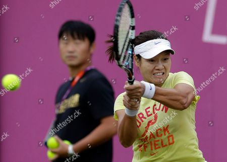 Li Na, Jiang Shan Li Na of China practices as her husband and coach, Jiang Shan, watches at the All England Lawn Tennis Club at Wimbledon, London at the 2012 Summer Olympics, . Tennis competition is scheduled to begin Saturday, July 28