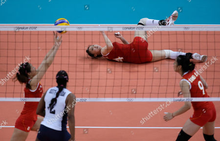 Stock Image of Danielle Scott-Arruda, Wei Qiuyue, Hui Ruoqi, Yang Junjing China's Hui Ruoqi, top, watches from the ground as teammate Wei Qiuyue, left, sets and Yang Junjing, right, looks on along with United States' Danielle Scott-Arruda, bottom, during a women's preliminary volleyball match at the 2012 Summer Olympics, in London