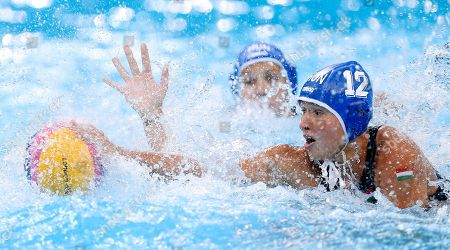 Katalin Menczinger of Hungary stretches for the ball as Rowie Webster of Australia hand is seen rising up during their women's water polo preliminary round match at the 2012 Summer Olympics, in London