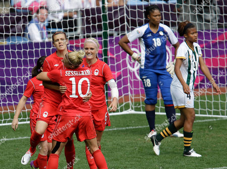 Canada's Christine Sinclair, center, is hugged by her teammate Lauren Sesselmann, after scoring during the group F women's soccer match between South Africa and Canada at the London 2012 Summer Olympics, in Coventry, England