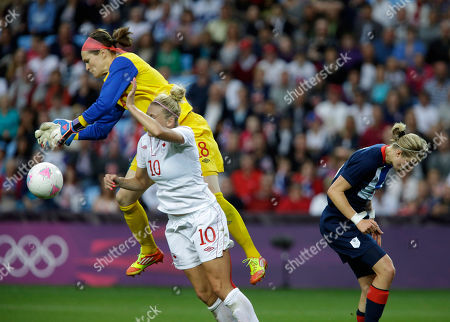 Canada's goalkeeper Erin Mcleod jumps over her teammate Lauren Sesselmann to saves the ball against Britain's Ellen White, right, during their quarterfinal women's soccer match at the 2012 London Summer Olympics, in Coventry, England