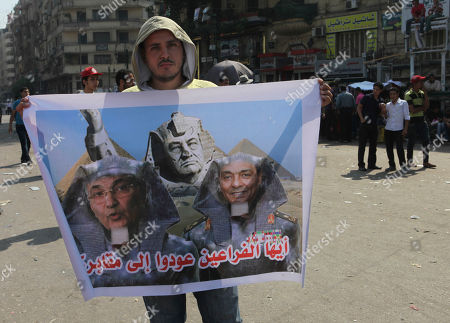"""An Egyptian man holds a poster with former presidential candidate, Ahmed Shafiq, left, ousted President Hosni Mubarak, center, and the head of the military council, Field Marshal Hussein Tantawi, right, depicted as pharaohs inTahrir Square, Cairo, Egypt, . The Muslim Brotherhood's Mohammed Morsi was declared the winner of Egypt's first free presidential election Sunday, and he proclaimed himself a leader """"for all Egyptians,"""" although he faces a struggle for power with the country's still-dominant military rulers. Arabic reads """"Pharaohs, go back to your tomb"""
