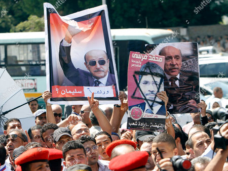 Egyptians raise defaced posters of Egyptian President Mohammed Morsi, center, and posters of Egypt's former spy chief Omar Suleiman, during Suleiman's military funeral in Cairo, Egypt, . The 76-year-old Suleiman died Thursday in a U.S. hospital. The shadowy statesman was considered Mubarak's most trusted man, handing the regime's most sensitive issues like relations with the U.S. and Israel and the fierce battle against Islamists