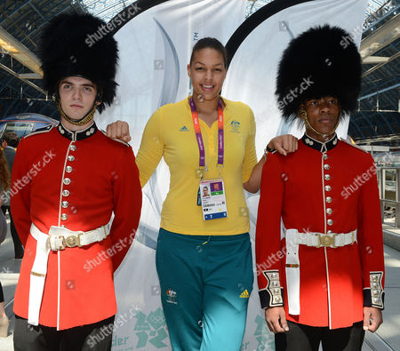 Australian women's basketball player Liz Cambage poses with actors upon arrival at the Eurostar Terminal at London St. Pancras Station ahead of the London 2012 Olympic Games on