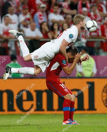 Poland's Damien Perquis jumps over Czech Republic's Milan Baros during the Euro 2012 soccer championship Group A match between Czech Republic and Poland in Wroclaw, Poland