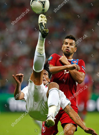Portugal's Bruno Alves clears the ball against Czech Republic's Milan Baros during the Euro 2012 soccer championship quarterfinal match between Czech Republic and Portugal in Warsaw, Poland