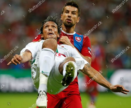 Portugal's Bruno Alves jumps to clear the ball against Czech Republic's Milan Baros during the Euro 2012 soccer championship quarterfinal match between Czech Republic and Portugal in Warsaw, Poland