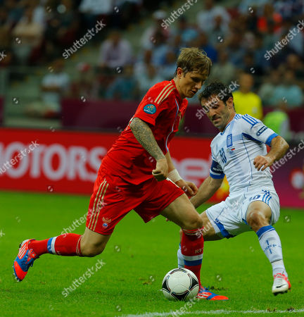 Russia's Roman Pavlyuchenko fight for the ball with Greece's Giorgos Karagounis during the Euro 2012 soccer championship Group A match between Greece and Russia in Warsaw, Poland