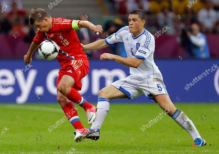 Russia's Andrei Arshavin, left, is challenged by Greece's Kyriakos Papadopoulos during the Euro 2012 soccer championship Group A match between Greece and Russia in Warsaw, Poland