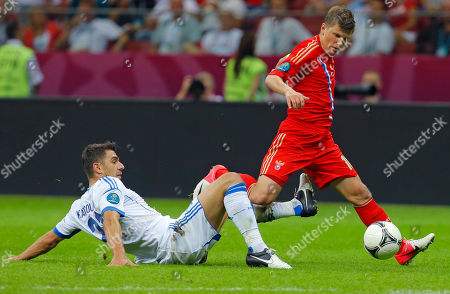 Greece's Costas Katsouranis challenges Russia's Andrei Arshavin during the Euro 2012 soccer championship Group A match between Greece and Russia in Warsaw, Poland