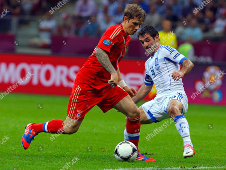 Stock Photo of Russia's Roman Pavlyuchenko, left, is challeneged by Greece's Giorgos Karagounis during the Euro 2012 soccer championship Group A match between Greece and Russia in Warsaw, Poland