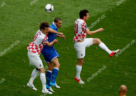 Italy's Leonardo Bonucci is flanked by Croatia's Nikica Jelavic, left, and Ivan Perisic during the Euro 2012 soccer championship Group C match between Italy and Croatia in Poznan, Poland
