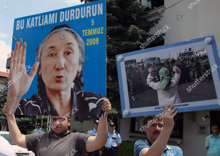 "Uighurs living in Turkey shout slogans as they stage a demonstration outside the Chinese embassy in Ankara, Turkey, to commemorate the third anniversary of deadly ethnic unrest in China's far-western Xinjiang Uighur Autonomous Region. The protesters carried placards that read ""Stop the Chinese Massacre against Uighurs"", "" 62 years occupation of East Turkistan by China"" and ""Freedom for Eastern Turkistan"" and waved the blue flag with a white star and a crescent representing Eastern Turkistan. The placard with a photo of Rebiya Kadeer, the most prominent Uighur dissident, reads: ""Stop this massacre"