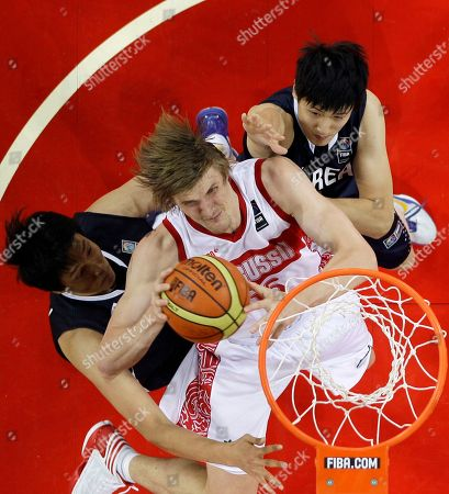 Russia's Andrei Kirilenko, center, goes up for a basket against the defense of South Korea's Lee Jong-hyun, left, and Choi Jin-soo during an Olympic basketball qualifier game in Caracas, Venezuela