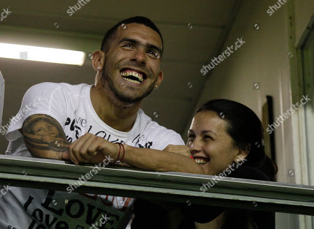 Stock Photo of England's Manchester City's soccer player Carlos Tevez, left, from Argentina, accompanied by his wife Vanesa Mansilla, laughs before a Copa Libertadores soccer match between Argentina's Boca Juniors and Brazil's Fluminense in Buenos Aires, Argentina