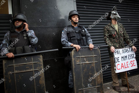 """A activist, right, wearing a donkey mask, stands next to police as they stand guard outside a military club during a protest in downtown Rio de Janeiro, Brazil, . A club of retired military officers held its annual celebration of Brazil's 1964 military coup as usual, but faced protestors as members arrived for the event. Unlike its Latin American neighbors, Brazil never had a formal investigation into its 20-year dictatorship. The sign reads in Portuguese """" Father keep that one away…shut-up,"""" a twist of words from a song by famous singer Chico Buarque which was censored during the dictatorship"""