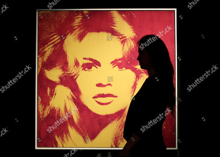 A Sotheby's employee poses with a 1974 portrait of Brigitte Bardot by Andy Warhol on display at the auction house in London, . The painting is part of Gunter Sachs Collection and is to be auctioned on May 22 and 23 with an estimated price of 3 to 4 million pounds (US$4.74 to 6.32 million or 3.73 to 4.94 million euro