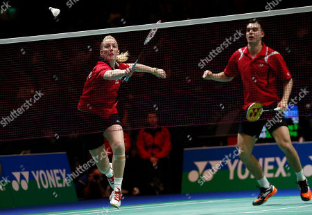 Scotland's Imogen Bankier, left, plays a shot on her way to defeat with her partner England's Chris Adcock to Malaysia's Liu Ying Goh and Peng Soon Chan in the mixed doubles quarterfinal at The All England Open Badminton Championships, Birmingham, England