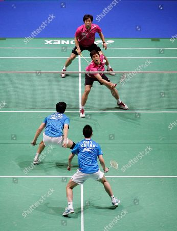 South Korea's Yong Dae Lee returns a shot as partner Jae Sung Jung, top, looks on and during their men's doubles final against China's Yun Cai and Haifeng Fu at The All England Open Badminton Championships, Birmingham, England