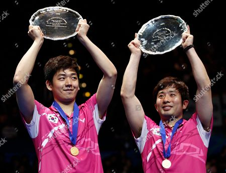 South Korea's Jae Sung Jung, right, and Yong Dae Lee hold their trophies as they celebrate their men's doubles final victory against China's Yun Cai and Haifeng Fu at The All England Open Badminton Championships, Birmingham, England