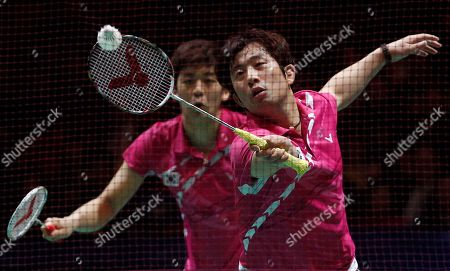 Seen through the net, South Korea's Jae Sung Jung, right, returns a shot as partner Yong Dae Lee looks on during their men's doubles final victory over China's Yun Cai and Haifeng Fu at The All England Open Badminton Championships, in Birmingham, England